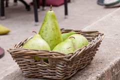 Fresh ripe pears in a wicker basket. Harvest of fresh ripe pears displayed in a wicker basket on a wall outdoors at a farmers market or for a quick delicious Stock Photography