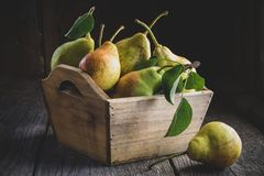 Fresh ripe pears in a wooden crate on table. Royalty Free Stock Photo