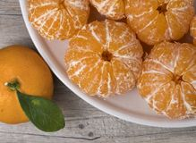 Fresh ripe peeled tangerine in a dish on a wooden background stock photo