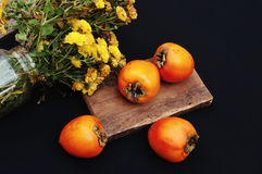 Fresh ripe persimmon on a black background . Persimmons fruit, Ripe sweet persimmons Stock Images