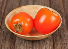 Fresh ripe persimmon in bowl on wooden table. Royalty Free Stock Images