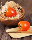 Fresh ripe persimmon in bowl on wooden table. Royalty Free Stock Photos