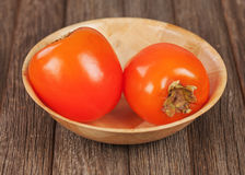 Fresh ripe persimmon in bowl on wooden table. Stock Images