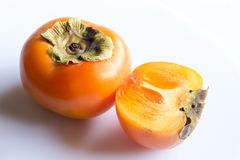 Close-up fresh ripe persimmons. Fresh ripe persimmons cut into half isolated on white background. Copy space Stock Photo