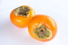 Close-up fresh ripe persimmons. Fresh ripe persimmons cut into half isolated on white background. Copy space Royalty Free Stock Images