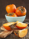 Fresh ripe persimmons on a wooden table. Stock Photos