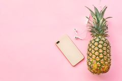 Fresh ripe pineapple with earphones and mobile phone. On color background, top view Royalty Free Stock Photo