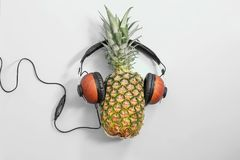 Fresh ripe pineapple with headphones. On color background, top view Royalty Free Stock Photos
