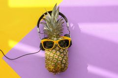 Fresh ripe pineapple with headphones. And sunglasses on color background, top view Royalty Free Stock Photos