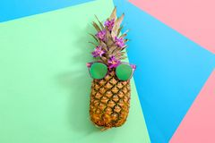 Fresh ripe pineapple with sunglasses. On color background, top view Royalty Free Stock Image