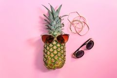 Fresh ripe pineapple with sunglasses. On color background, top view Royalty Free Stock Photo
