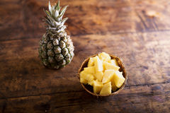 Fresh ripe pineapple, whole and chopped in a bowl. Fresh ripe pineapple, whole and chopped, laid on a table. Studio shot on old wooden background Royalty Free Stock Photo