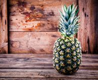 Fresh ripe pineapple on wooden background. Fresh ripe pineapple on wooden rustic background Royalty Free Stock Photo