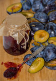 Fresh ripe plum - raw materials for making homemade jam and a glass jar with jam Stock Image