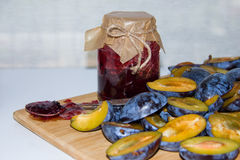Fresh ripe plum - raw materials for making homemade jam and a glass jar with jam Royalty Free Stock Photography