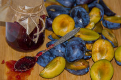 Fresh ripe plum - raw materials for making homemade jam and a glass jar with jam Royalty Free Stock Photos