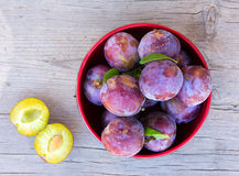 Fresh ripe plums in a red circular plate on old gray wooden board closeup Stock Photo