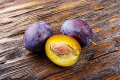 Fresh ripe plums top view. Fresh ripe plums on a brown wooden background, top view Royalty Free Stock Photography