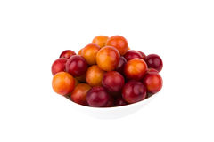 Fresh ripe plums in a white plate isolated on white background Stock Photos