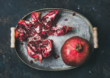 Fresh ripe pomegranate broken in metal tray over plywood background. Fresh ripe pomegranate in vintage metal tray over dark blue plywood background, top view Stock Images