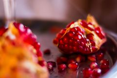 Fresh ripe pomegranate on a dark background.garnet in the section. pomegranate.Fresh organic fruits. Red and juicy seeds. Fresh ripe pomegranate on a dark wooden Stock Image
