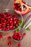 Fresh ripe pomegranate seeds on a glass plate. Wooden background Stock Photo
