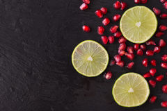 Fresh ripe pomegranate seeds and lime slices on wet black stone stock photography