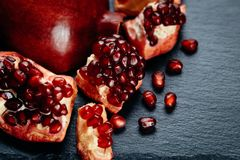 Fresh ripe pomegranate on a slate plate kitchen table.  Royalty Free Stock Photo