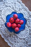 Fresh ripe radishes in a blue glass salad bowl on a wooden table with beautiful white tablecloth. Top view royalty free stock images