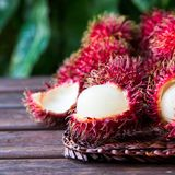 Fresh ripe rambutans on wooden background. Delicious rambutan sw. Eet fruit Stock Photography