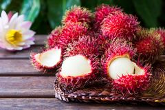 Fresh ripe rambutans on wooden background. Delicious rambutan sw. Eet fruit Stock Images