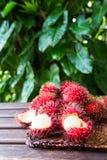 Fresh ripe rambutans on wooden background. Delicious rambutan sw. Eet fruit Royalty Free Stock Photos