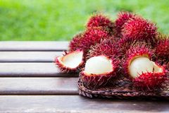 Fresh ripe rambutans on wooden background. Delicious rambutan sw. Eet fruit Royalty Free Stock Photography