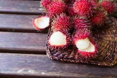 Fresh ripe rambutans on wooden background. Delicious rambutan sw. Eet fruit Royalty Free Stock Image