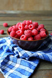 Fresh and ripe raspberries in a bowl on a wooden table. Food close up Stock Image