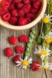 Fresh ripe raspberries and camomile flowers Royalty Free Stock Photo