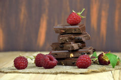 Fresh ripe raspberries and chocolate. Yummy. Dark chocolate with raisins and nuts stackя.  with fresh raspberries, on wooden table./ selective focus./ Close-up Stock Photography