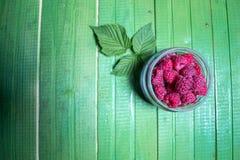 Fresh ripe raspberries on green wooden boards. Stock Photos