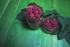 Fresh ripe raspberries on green wooden boards. Stock Photo