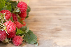 Fresh ripe raspberries with large leaves. On the old wooden table with copy space Royalty Free Stock Photo