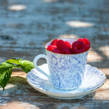Fresh ripe raspberries and an old porcelain cup with a saucer on a wooden table in the garden. Royalty Free Stock Image