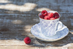 Fresh ripe raspberries and an old porcelain cup with a saucer on a wooden table in the garden. Stock Image