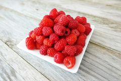 Fresh ripe raspberry on white plate, isolated on wooden table or background Royalty Free Stock Photography