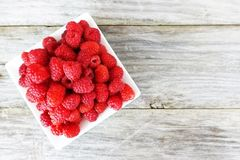 Fresh ripe raspberry on white plate, isolated on wooden table or background. Fresh ripe raspberry on white plate, isolated on wooden table Stock Photo