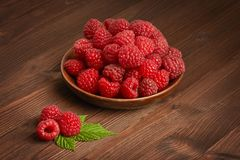 Fresh ripe raspberry in a wooden plate and a few berries next to. A wooden brown color Royalty Free Stock Image
