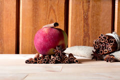 Fresh ripe red apple and cinnamon sticks on wooden background. Fresh ripe red apple and cinnamon sticks on wooden background Royalty Free Stock Images
