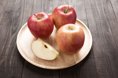 Fresh ripe red apples on dish wooden background Royalty Free Stock Images