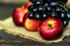 Fresh ripe red apples and grapes on burlap napkin Stock Images
