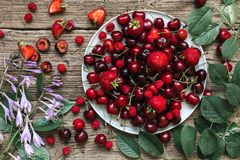 Fresh ripe red berries - cherry, strawberry and raspberry on a plate with summer flowers on rustic wooden background. Fresh ripe berries. top view Royalty Free Stock Image
