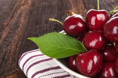 Fresh ripe red cherries. In a white bowl on wooden table Stock Photos